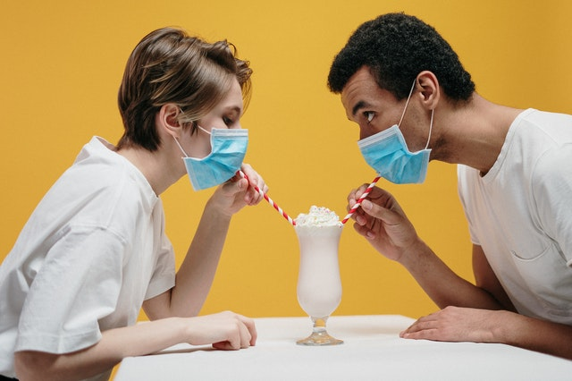couple sipping a milkshake through their masks